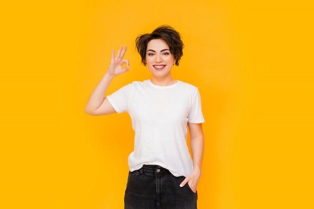 Młoda szczęśliwa brunetki kobieta z krótkim ostrzyżeniem w białej koszulce na żółtym tle. portret młodej kobiety z różnymi emocjami na żółtym tle. miejsce na tekst