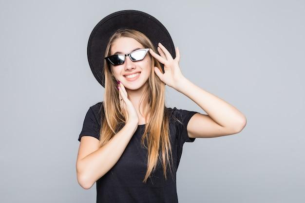 Młoda szczęśliwa całkiem uśmiechnięta dama w genialnych okularach przeciwsłonecznych ubrana w czarny kapelusz, czarną koszulkę i ciemne spodnie na białym tle na szarym tle