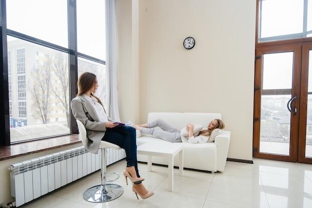 Młoda szczęśliwa dziewczyna komunikuje się z psychologiem w nowoczesnym gabinecie. pomoc psychologiczna.