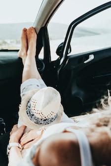 Młoda szczęśliwa dziewczyna odpoczywa w samochodzie z otwartymi drzwiami nad morzem na plaży w słoneczny letni dzień