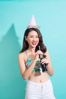 Młoda szczęśliwa dziewczyna pije koks z butelki na kolorowym niebieskim tle