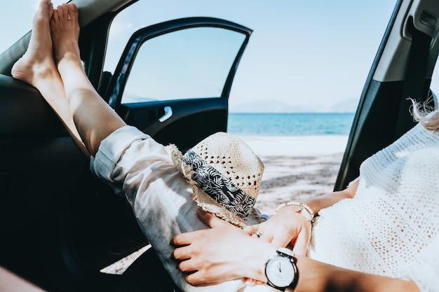 Młoda szczęśliwa dziewczyna po odpoczynku w samochodzie z otwartymi drzwiami nad morzem na plaży w słoneczny letni dzień. koncepcja podróży i wakacji.