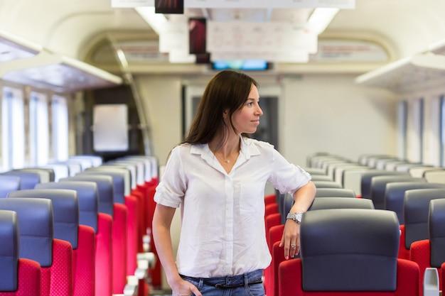 Młoda szczęśliwa dziewczyna podróżuje pociągiem