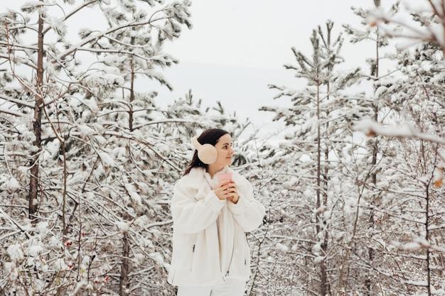 Młoda szczęśliwa dziewczyna w białych ubraniach i puszystych słuchawkach w górach trzyma różową filiżankę kawy w śnieżnym czasie.