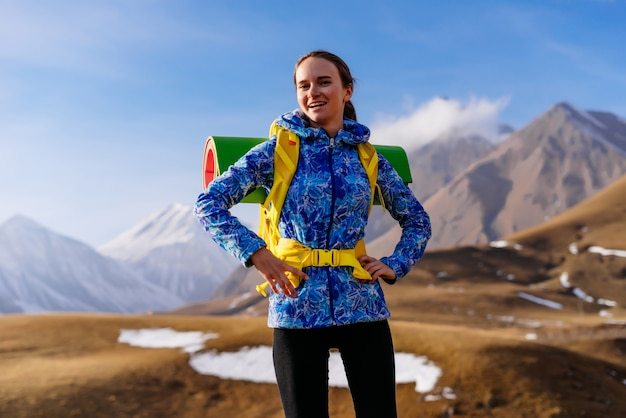 Młoda szczęśliwa dziewczyna w niebieskiej kurtce podróżuje wzdłuż kaukaskiego grzbietu z plecakiem i namiotem