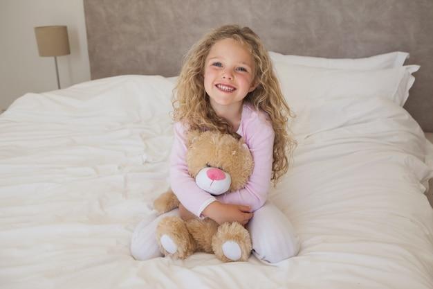 Młoda szczęśliwa dziewczyna z faszerującym zabawkarskim obsiadaniem na łóżku