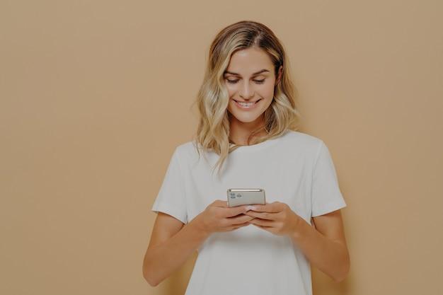 Młoda szczęśliwa dziewczyna za pomocą smartfona rozmawiającego z chłopakiem w mediach społecznościowych i uśmiechnięta
