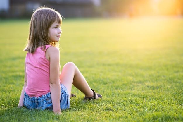 Młoda szczęśliwa dziewczynka odpoczynek siedząc na zielonej trawie trawnik w ciepły letni dzień.