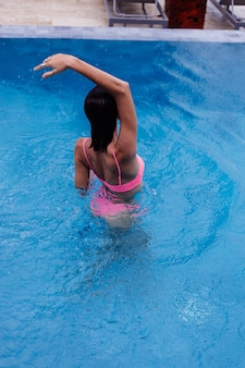 Młoda szczęśliwa fit szczupła europejska kobieta w jasny różowy bikini niebieski basen