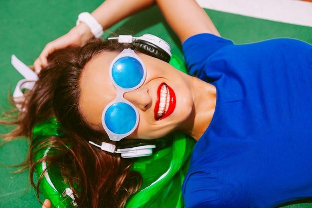 Młoda szczęśliwa hipster dziewczyna leży na jej przezroczystym neonowym plecaku, słuchając ulubionej muzyki i ciesząc się letnią reklamą swoich wakacji. ma idealnie białe zęby i lśniące, czerwone usta.