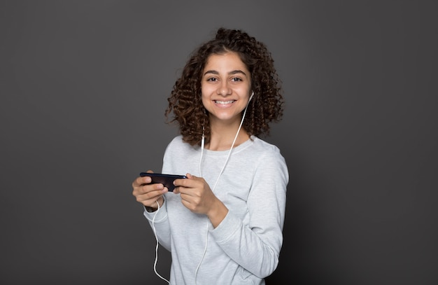 Młoda szczęśliwa indyjska brunetka kobieta słucha muzyki na słuchawkach na smartfonie.