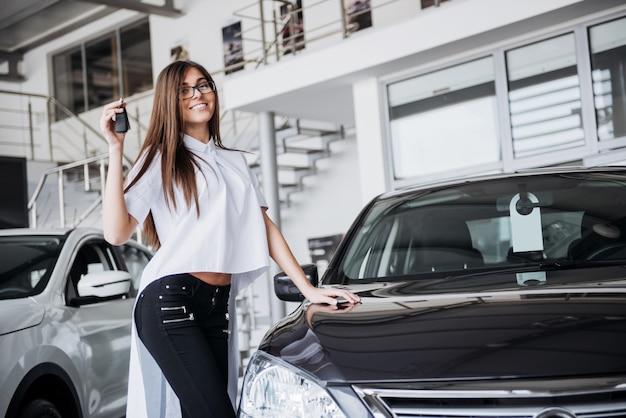 Młoda szczęśliwa kobieta blisko samochodu z kluczami w ręce