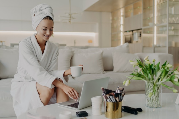 Młoda szczęśliwa kobieta blogerka piękna w szlafroku i ręczniku na głowie, siedząca na wygodnej kanapie w nowoczesnym salonie i pracująca na laptopie, pijąca herbatę i zrelaksowana po wzięciu prysznica w domu