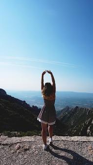 Młoda szczęśliwa kobieta ciesząca się wspaniałym widokiem na góry montserrat