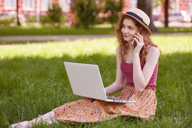 Młoda szczęśliwa kobieta dzwoni z inteligentnego telefonu podczas przerwy między pracą na komputerze przenośnym, uśmiechnięta studentka rozmawia przez telefon komórkowy, siedząc z książką w parku w czasie rekreacji