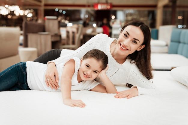 Młoda szczęśliwa kobieta i mała dziewczynka na materac