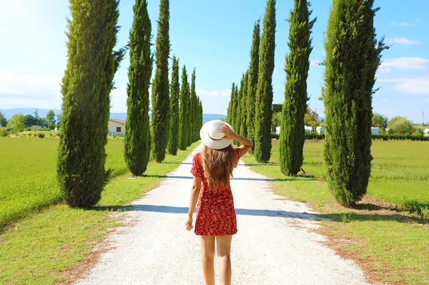 Młoda szczęśliwa kobieta idzie na ścieżce z typowym krajobrazem toskanii