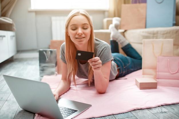 Młoda szczęśliwa kobieta jest gotowa wydawać pieniądze z karty bankowej męża, leżąc na podłodze z torbami na zakupy