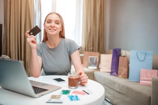 Młoda szczęśliwa kobieta jest gotowa wydawać pieniądze z karty płatniczej, siedząc przy stole