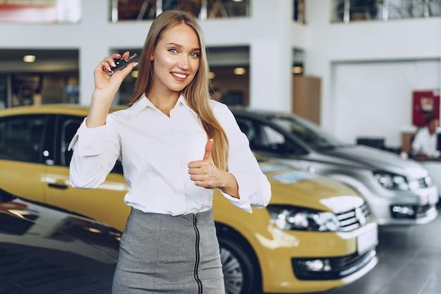 Młoda szczęśliwa kobieta kupujący / sprzedający w pobliżu samochodu z kluczami w ręku