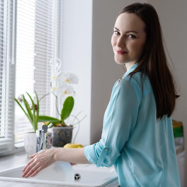 Młoda szczęśliwa kobieta myje naczynia w zlew przed okno, miękki wczesnego poranku światło