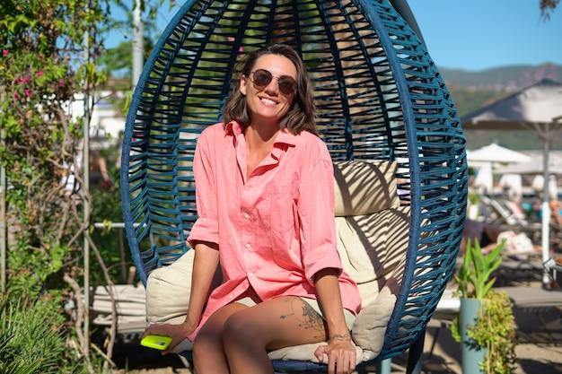 Młoda szczęśliwa kobieta na plaży w upalny letni dzień w sukience się śmieje