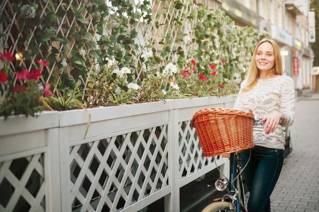Młoda szczęśliwa kobieta na rocznika bicyklu