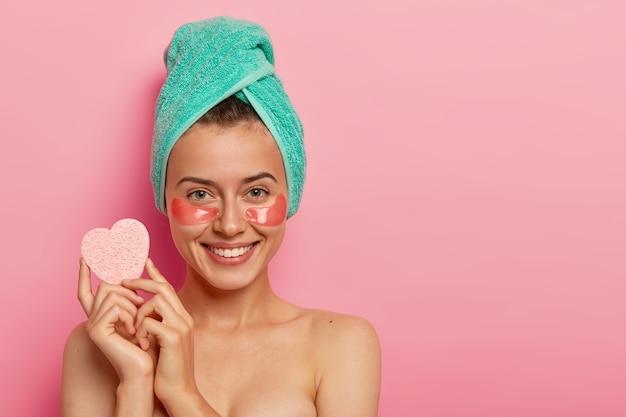 Młoda szczęśliwa kobieta nosi kolagenowe plastry nawilżające pod oczami, trzyma gąbkę do zmywania makijażu, wykonuje zabiegi kosmetyczne, ma świeżą skórę po prysznicu