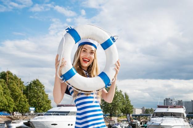 Młoda szczęśliwa kobieta o kaukaskim wyglądzie w niebieskiej sukience w paski stojąca na jachcie pozuje z kołem ratunkowym w dłoni na tle błękitnego nieba z chmurami w letni słoneczny dzień