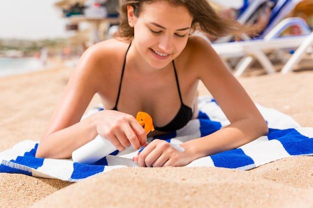 Młoda szczęśliwa kobieta odpoczywa na ręczniku w pobliżu morza i chroni skórę dłoni kremem przeciwsłonecznym przed rozpryskami.