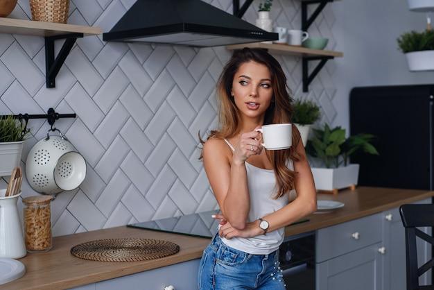 Młoda szczęśliwa kobieta pije kawę na kuchni w ranku