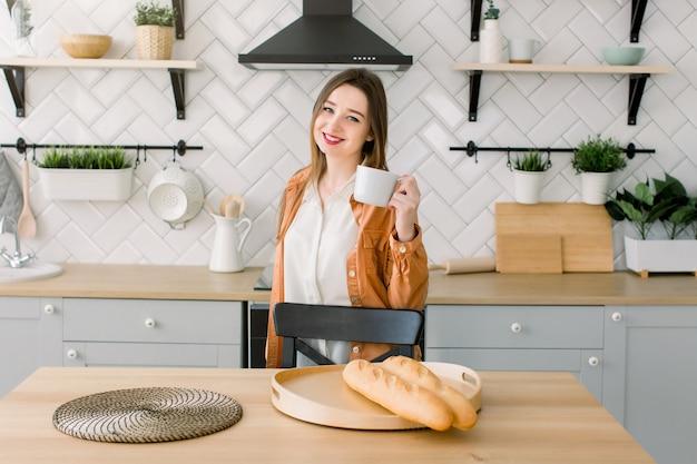 Młoda szczęśliwa kobieta pije kawę na kuchni w ranku.