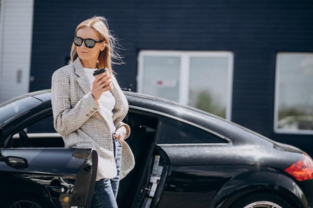 Młoda szczęśliwa kobieta pije kawę samochodem