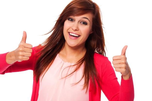 Młoda szczęśliwa kobieta pokazuje aprobaty