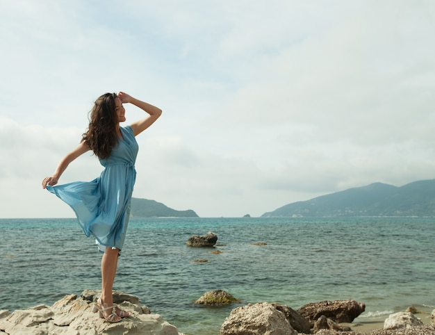 Młoda szczęśliwa kobieta pozuje blisko morza