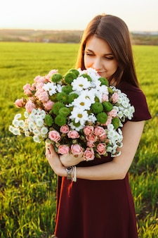 Młoda szczęśliwa kobieta pozuje z dużym bukietem przeciw zmierzchowi na polu
