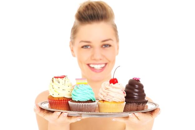 Młoda szczęśliwa kobieta pozuje z tacą babeczek