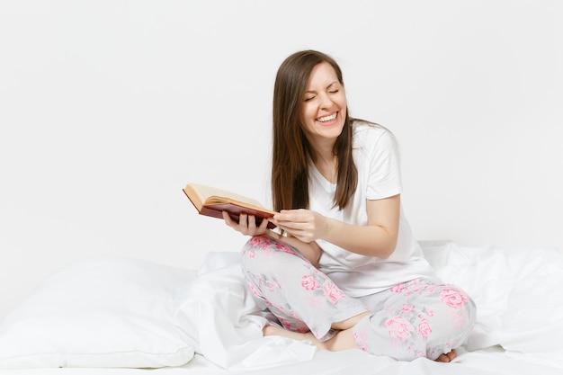Młoda szczęśliwa kobieta siedzi w łóżku z białym prześcieradłem, poduszką, kocem na białej ścianie