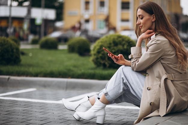 Młoda szczęśliwa kobieta siedzi w parku i rozmawia przez telefon