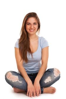 Młoda szczęśliwa kobieta siedzi