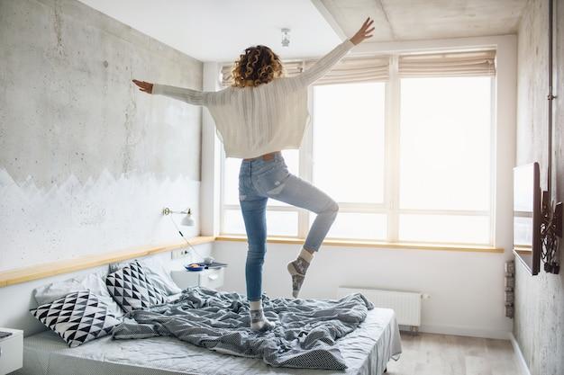 Młoda szczęśliwa kobieta skacze na łóżku w godzinach porannych