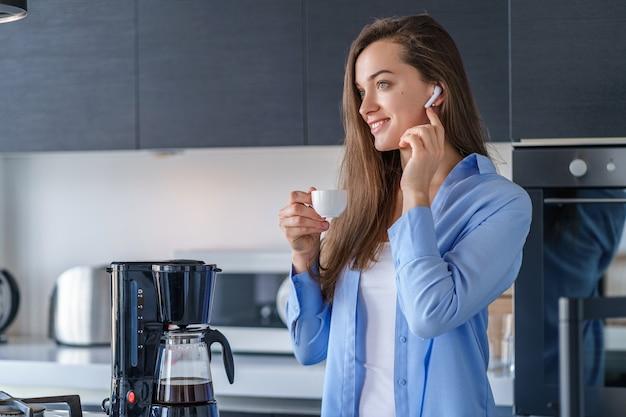 Młoda szczęśliwa kobieta słucha muzykę i audio książkę z białymi bezprzewodowymi hełmofonami podczas picia świeżej aromatycznej kawy w kuchni w domu. współcześni mobilni ludzie