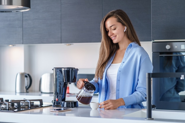 Młoda szczęśliwa kobieta słucha muzykę i audio książkę z białymi bezprzewodowymi słuchawkami podczas robić świeżej aromatycznej kawie używać kawowego producenta w kuchni w domu. współcześni mobilni ludzie