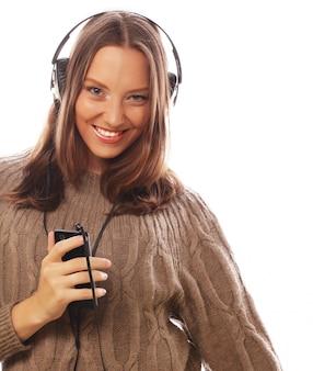 Młoda szczęśliwa kobieta słucha muzykę z hełmofonami