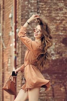 Młoda szczęśliwa kobieta spaceru po ulicy w krótkiej sukience, słuchając muzyki i tańca