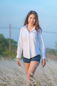 Młoda szczęśliwa kobieta stojąca w polu w świetle słońca