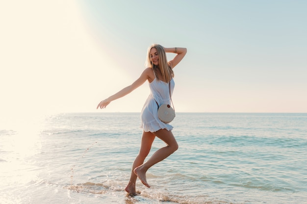 Młoda szczęśliwa kobieta tańczy odwracając się nad morzem na plaży w słoneczny letni styl mody w białej sukni wakacje