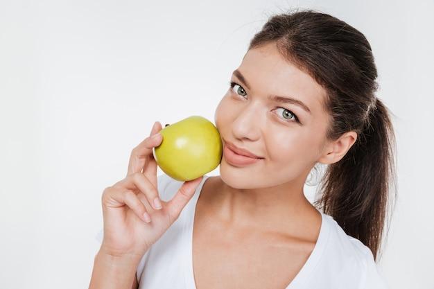 Młoda szczęśliwa kobieta trzyma jabłko w pobliżu twarzy na białym tle na białej ścianie.