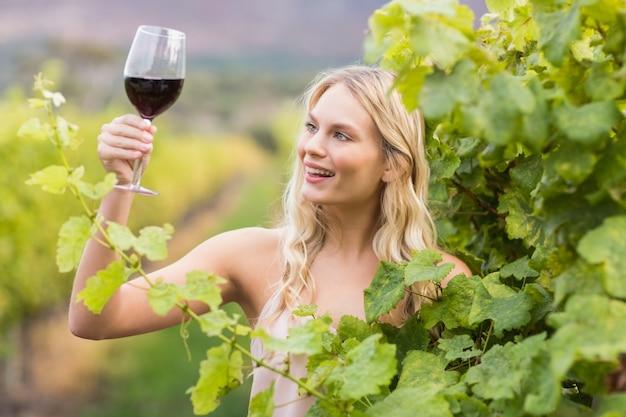 Młoda szczęśliwa kobieta trzyma szkło wino