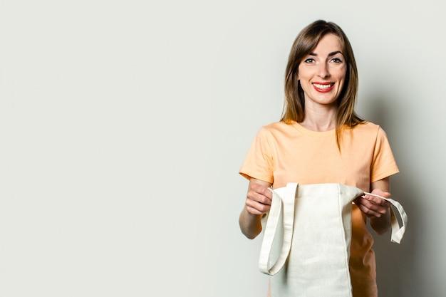 Młoda szczęśliwa kobieta trzyma torbę z zakupami na lekkim tle.